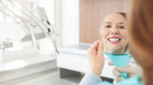 older woman looking at her teeth in a mirror
