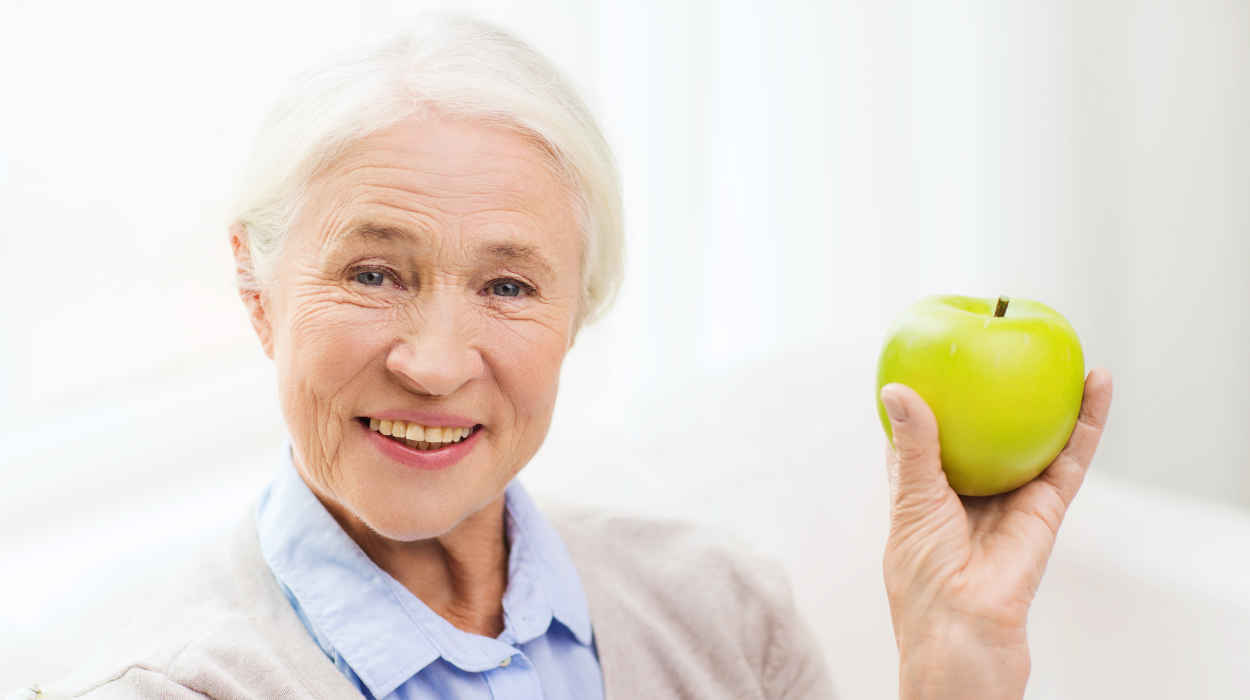 smiling older woman with an apple